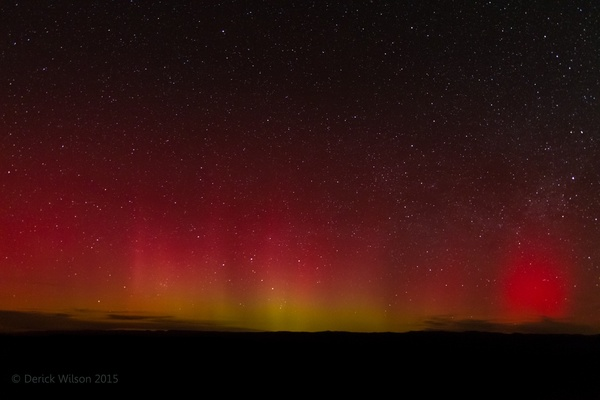 An aurora, yellowish at the bottom, fades to red at the top across a starry night background.