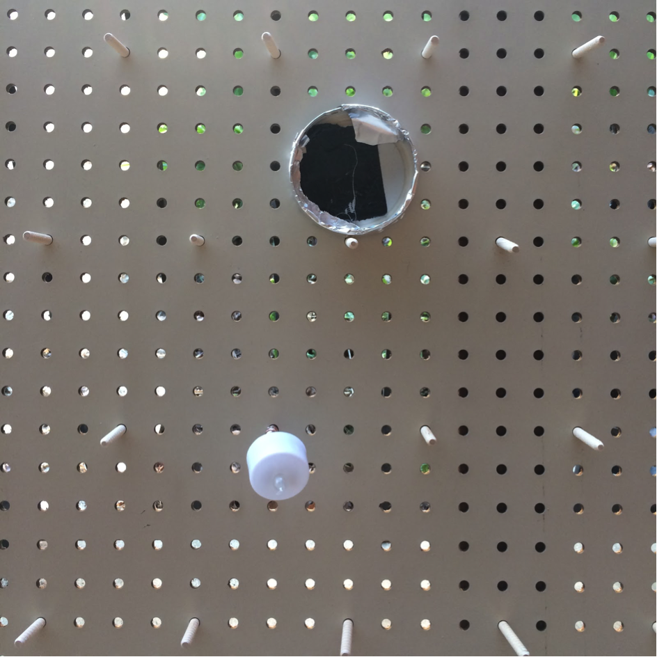 A pegboard with wooden dowels, an LED tea light, and a can lid (weighted with pennies covered by black duct tape and wrapped with Al foil). Note construction can be much improved.