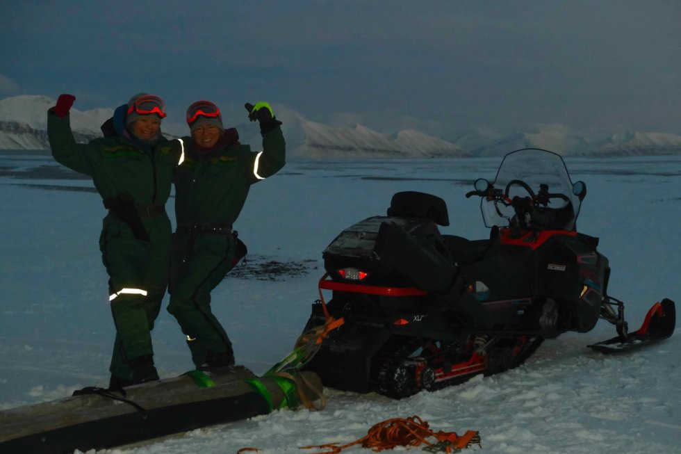 Two women strike a power pose, each with an arm around the other's shoulder. They are standing next to a snowmobile on a snowy landscape. The lighting is dark but reflective strips on their clothes glow bright.