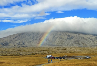 A rainbow reaches from a gray-brown lava field up in front of the craggy slopes of a broad volcano to the thick cloud covering its summit. Above, blue sky is striped and dotted with fluffy white clouds. In front of the lava field is a gold plain with a small parking lot, toward which a few people are walking.