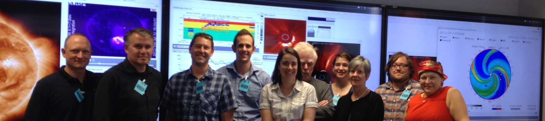 Ten people stand in front of screens that show space weather data