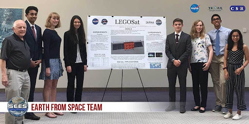Seven high schoolers in business attire and a middle-aged man stand beside a poster titled LEGOSat.