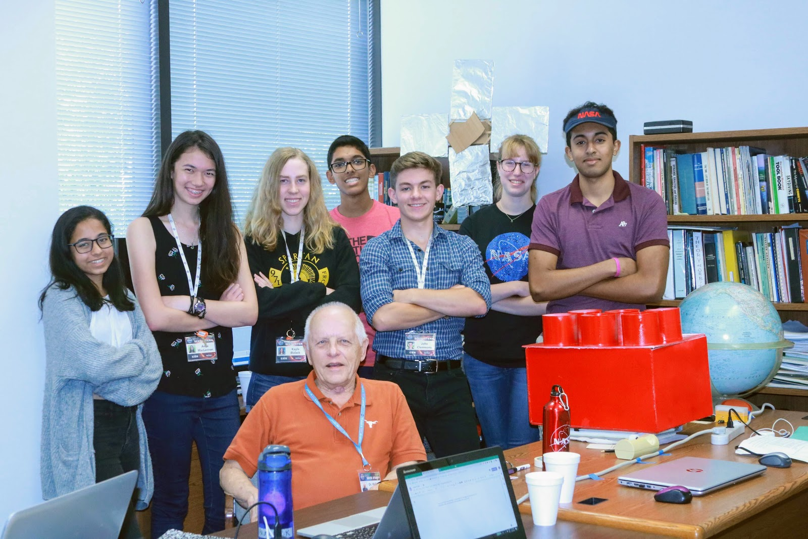 Seven high school students stand smiling with their arms folded behind their mentor, who is seated at a desk. On the desk is a tablet, along with white cups, a laptop, a globe, and a prototype that looks like a large red LEGO block.