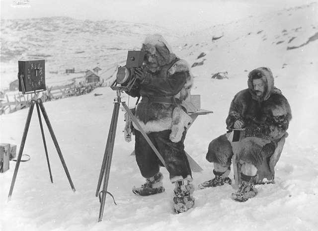 A man bundled in furs stands in the snow behind an old-fashioned camera, while another man, also bundled in furs, sits behind him making notes in a notebook.
