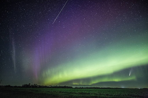 A landscape with a sky crossed by green and purple bands of aurora, along with other sky phenomena: STEVE, the ISS, and Comet NEOWISE.