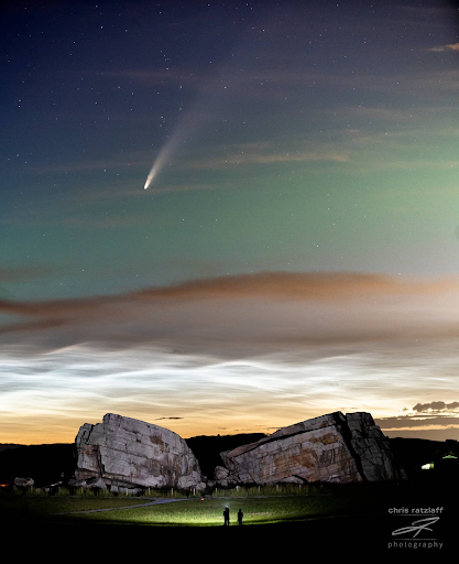 Behind large rocks, noctilucent clouds cross the sky. Above them is the glow of aurora, and at the top, the comet NEOWISE