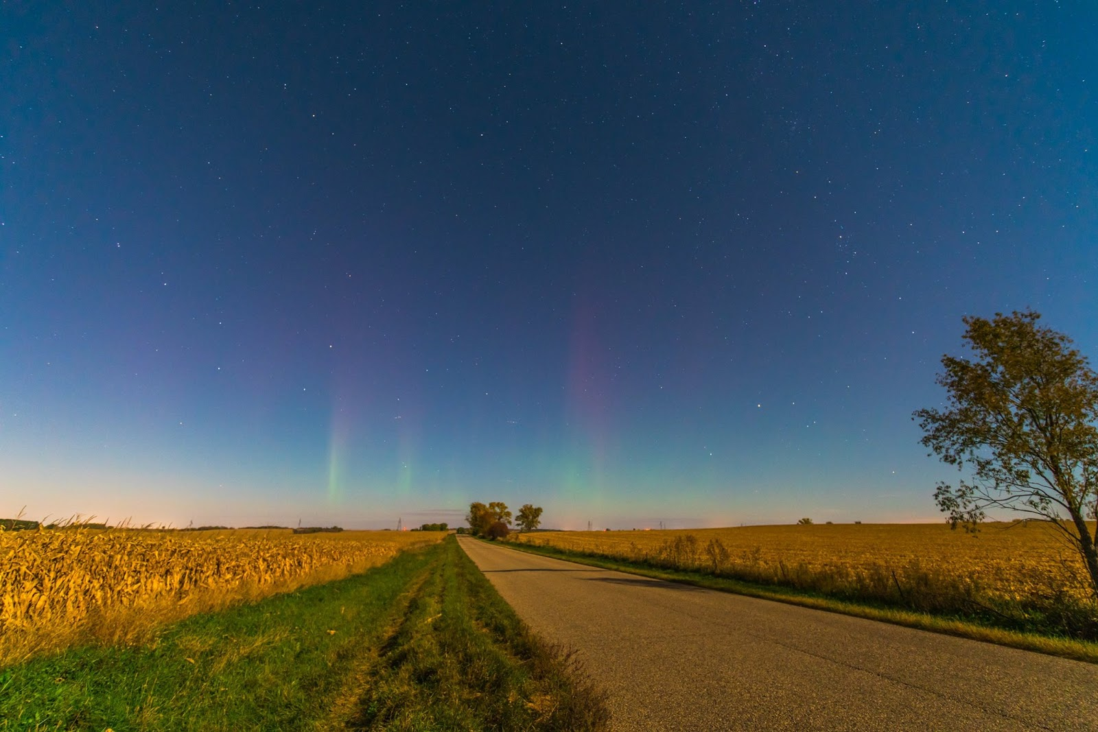 A colorful photo of a flat landscape shows faint green and red aurora pillars