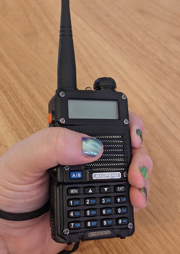 Laura's hand (complete with fabulous aurora nail wraps) grips a device like a walkie-talkie