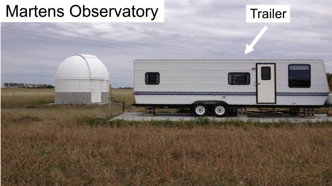 A telescope dome and a trailer in a field