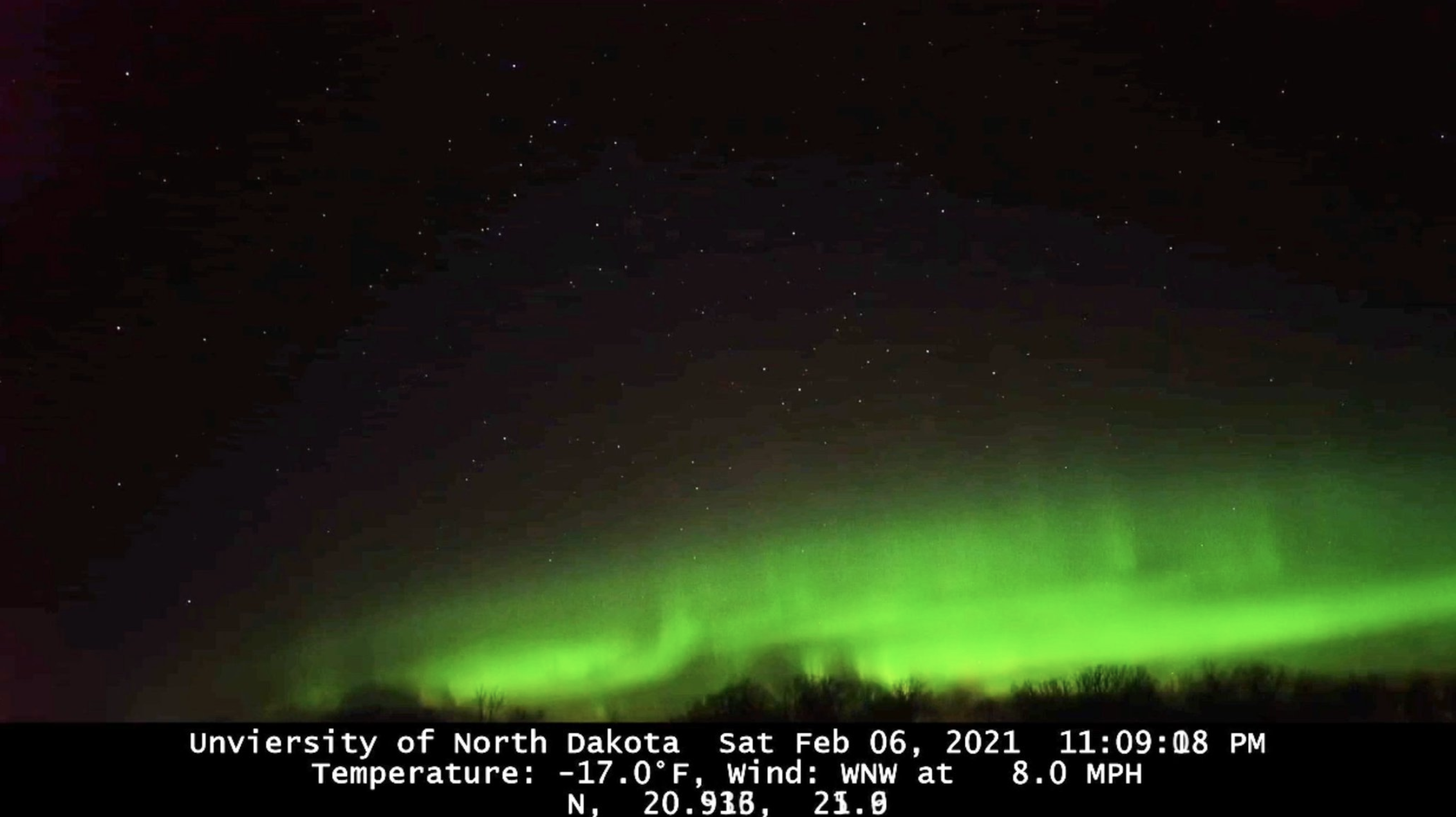 Green aurora against a black background with data listed at the bottom of the image