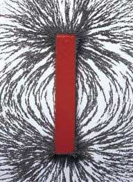 A red bar magnet is surrounded by iron filings taking the shape of a dipolar magnetic field