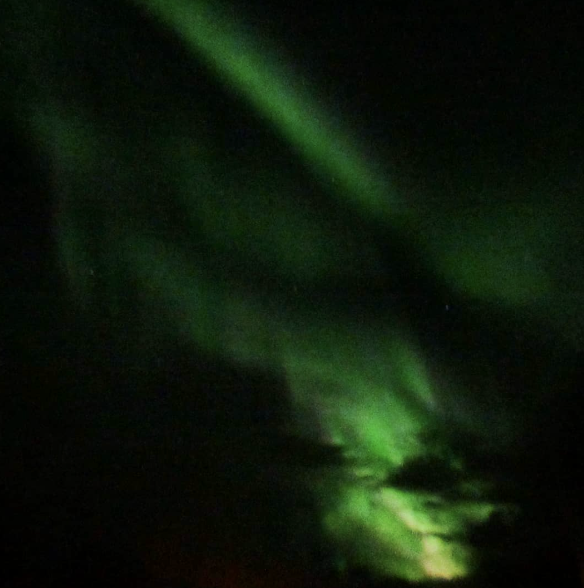 A somewhat blurry green glow waves across the dark of night