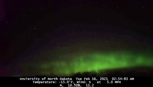 Green aurora against a dark sky. At the bottom of the image, text reads: University of North Dakota, Tue Feb 16, 2021 02:54 am Temperature: -15.0 degrees F, wind S at 5.0 mph. N, 12.520, 11.2