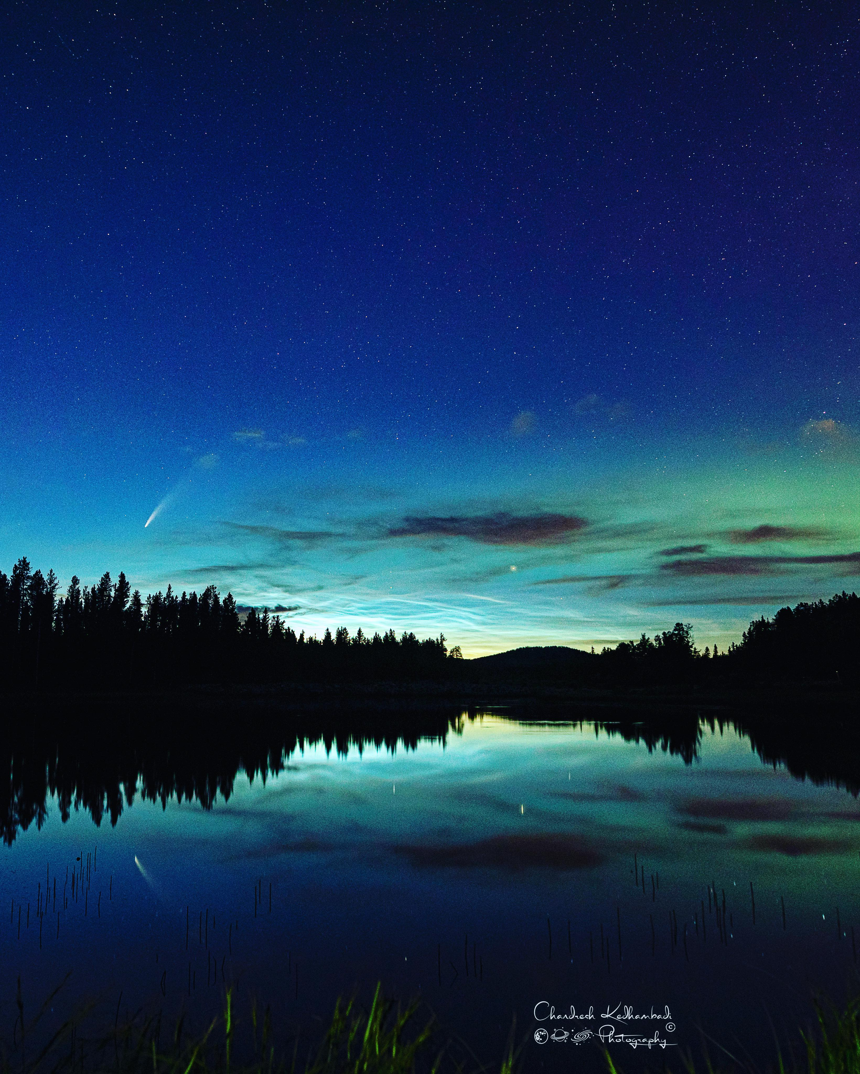 A landscape in front of water, with noctilucent clouds near the horizon
