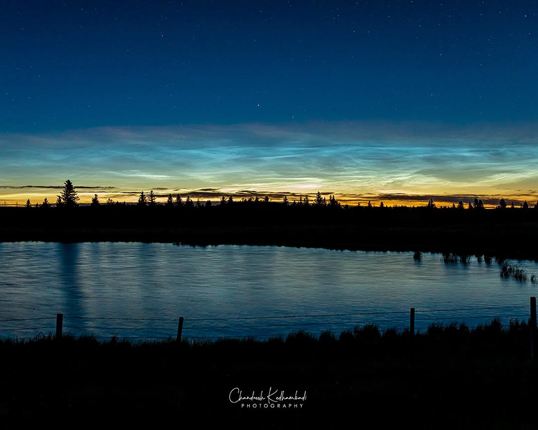 noctilucent clouds streak the sky above a landscape and water.