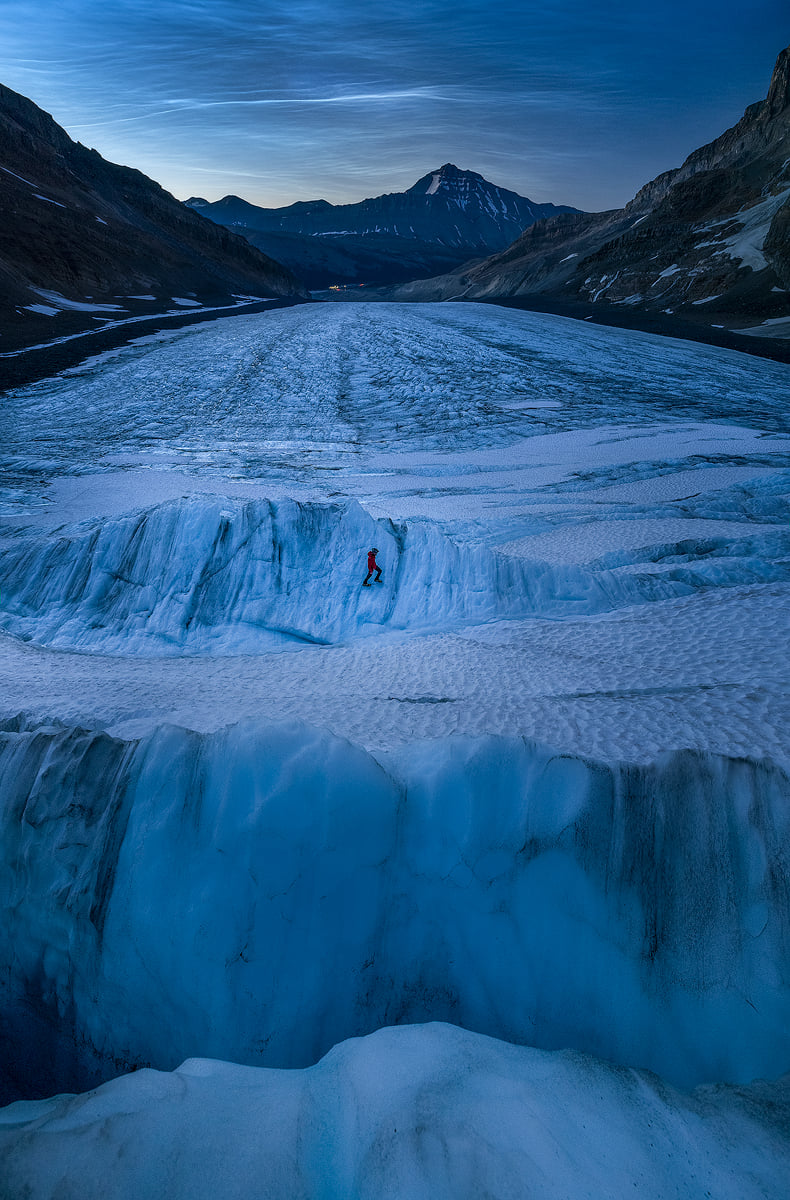 A person walks on a glacier beneath mountains and noctilucent clouds