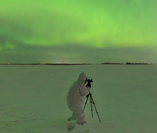 A man stands in snow taking a photo of aurora