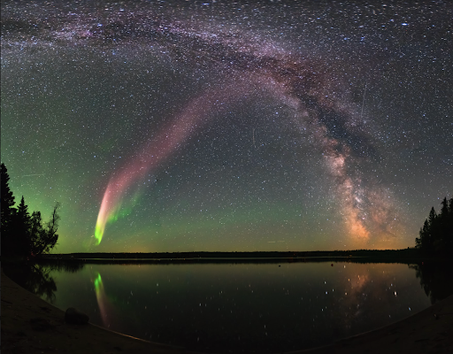 Aurora, STEVE, and stars light the sky and reflect in water